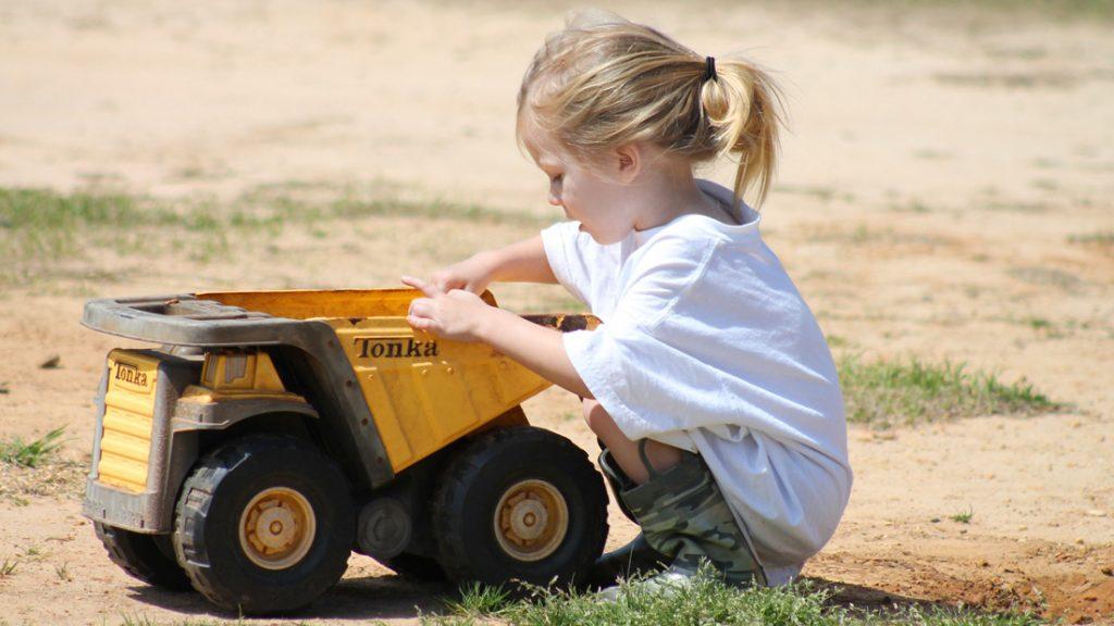 Ein kleines Mädchen spielt draußen mit ihrem Laster im Sand