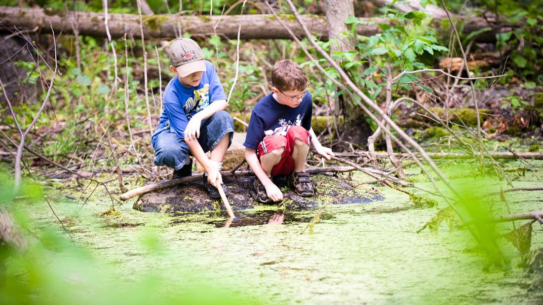 Zwei naturverbundende Jungs spielen mit Stöckern am Wasser eines Sees