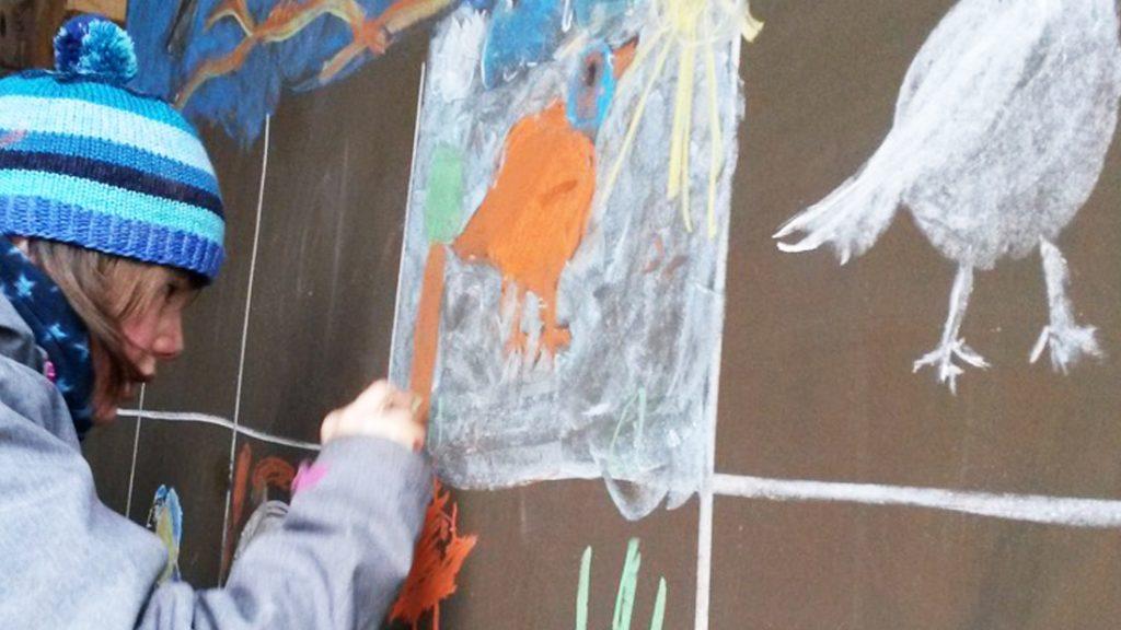 Ein Mädchen malt mit viel Eifer ein Bild mit einem Vogel an die Tafel