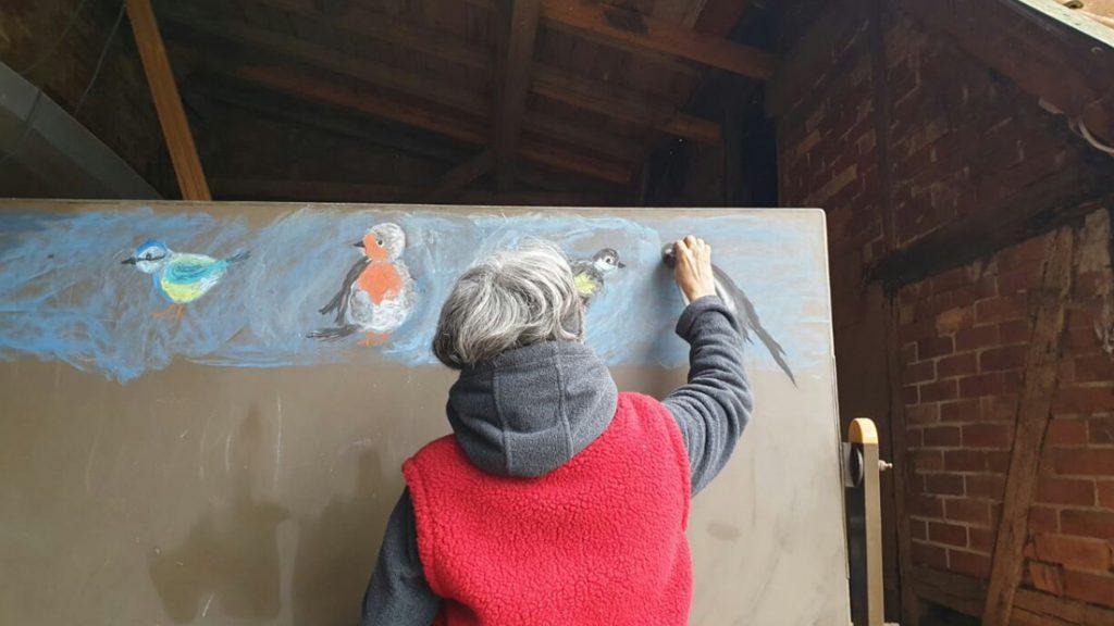 Das Tafelbild wird mit schönen Illustrationen von Vögeln vorbereitet und lädt zum Malen ein