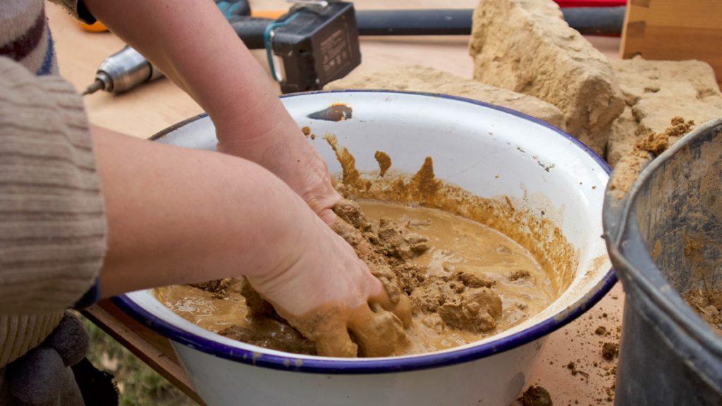 Die Kinder fertigten mit ihren Händen den Lehm in einer Schüssel an