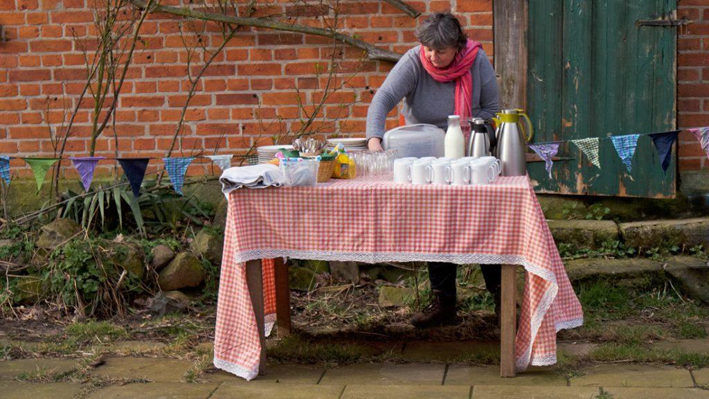 Susanne deckt im LERNORT-Garten den Tisch mit leckerem Kuchen und Getränken