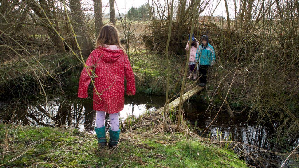 Kinder überqueren den Bach über den Holzsteg und erleben die Natur