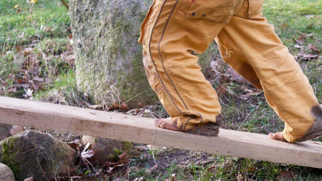 Ein kleiner Junge balanciert mit nackten Füßen über ein Brett